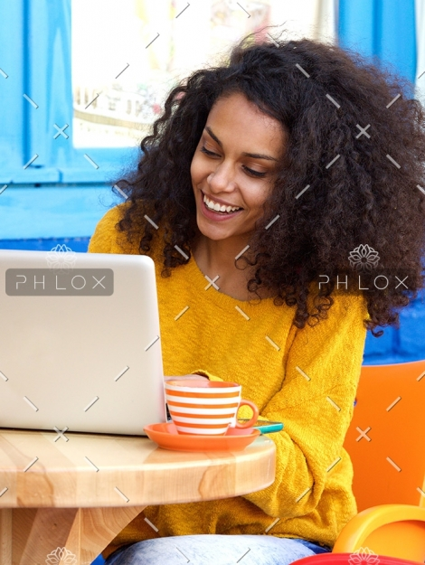 happy-young-woman-sitting-at-outdoor-cafe-using-PFFBJ93